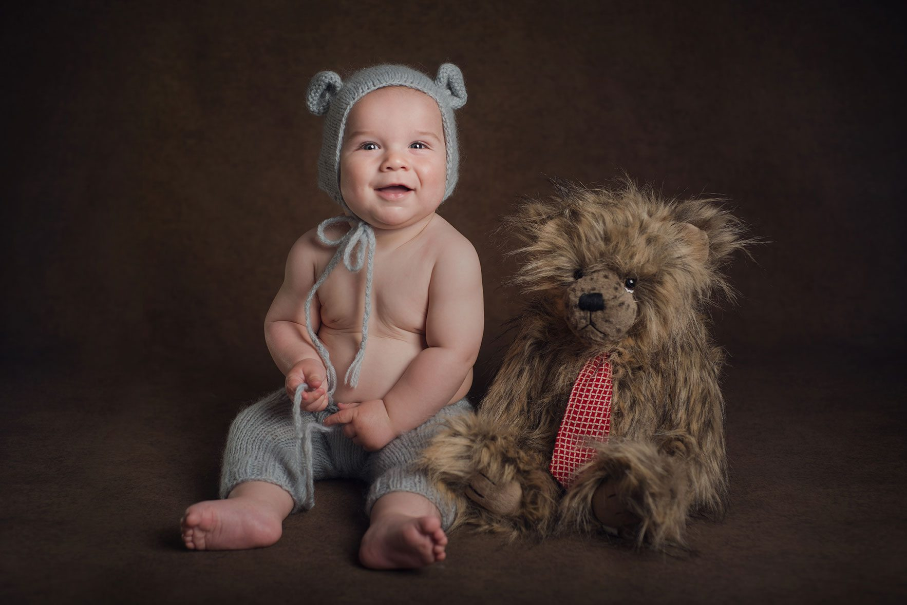 Baby boy studio photograph sitting with a bear wearing a bear hat.