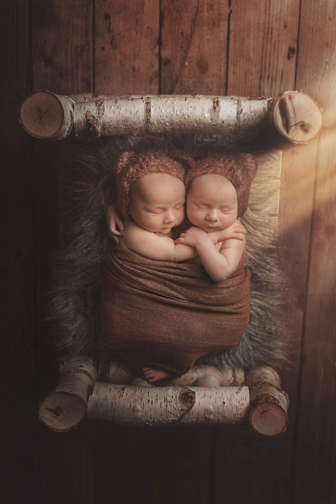 Baby boy twins cuddling on their newborn shoot in a bed.