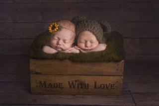 Twin boy and girl photoshoot laying cuddling in box.