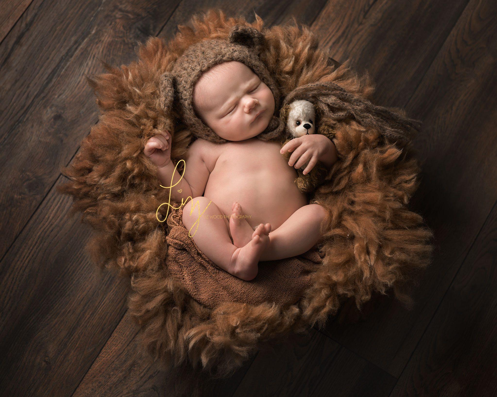 Essex baby photographer, bear ear hat on a cute sleeping newborn baby boy, laying on an Alpaca fleece.