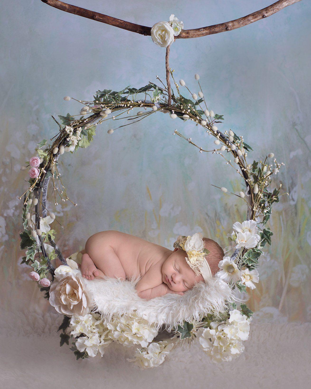 Safe baby composite newborn baby girl wearing a flower headband on a flower hoop - Essex and Suffolk baby photographer.