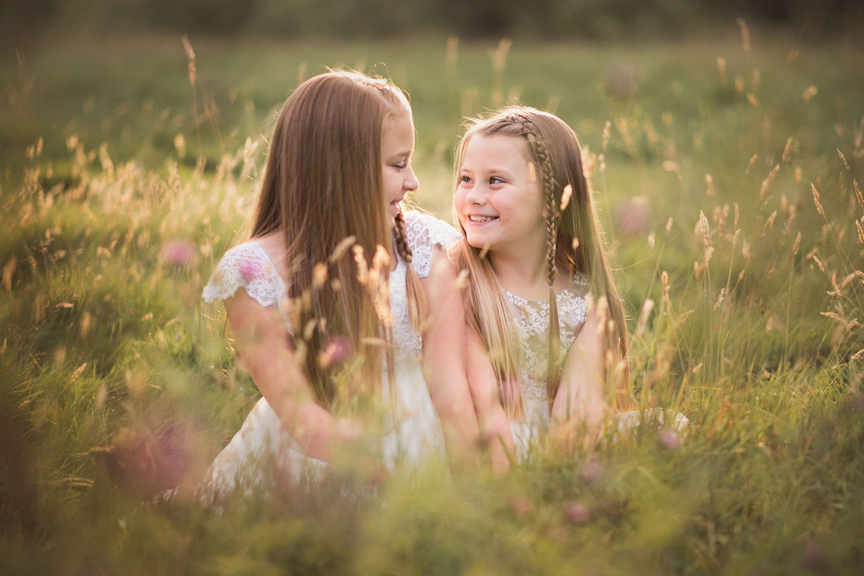 Girls sitting in golden light smiling at each other in field - Suffolk children's photographer