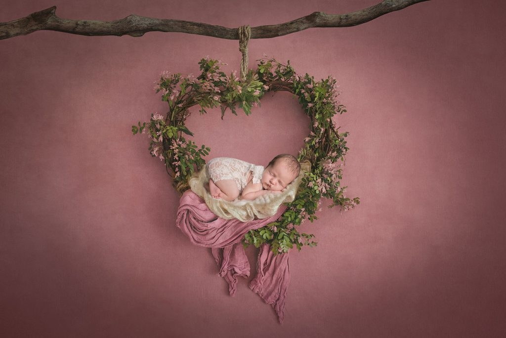 Beautiful heart shaped wreath with a sleeping newborn