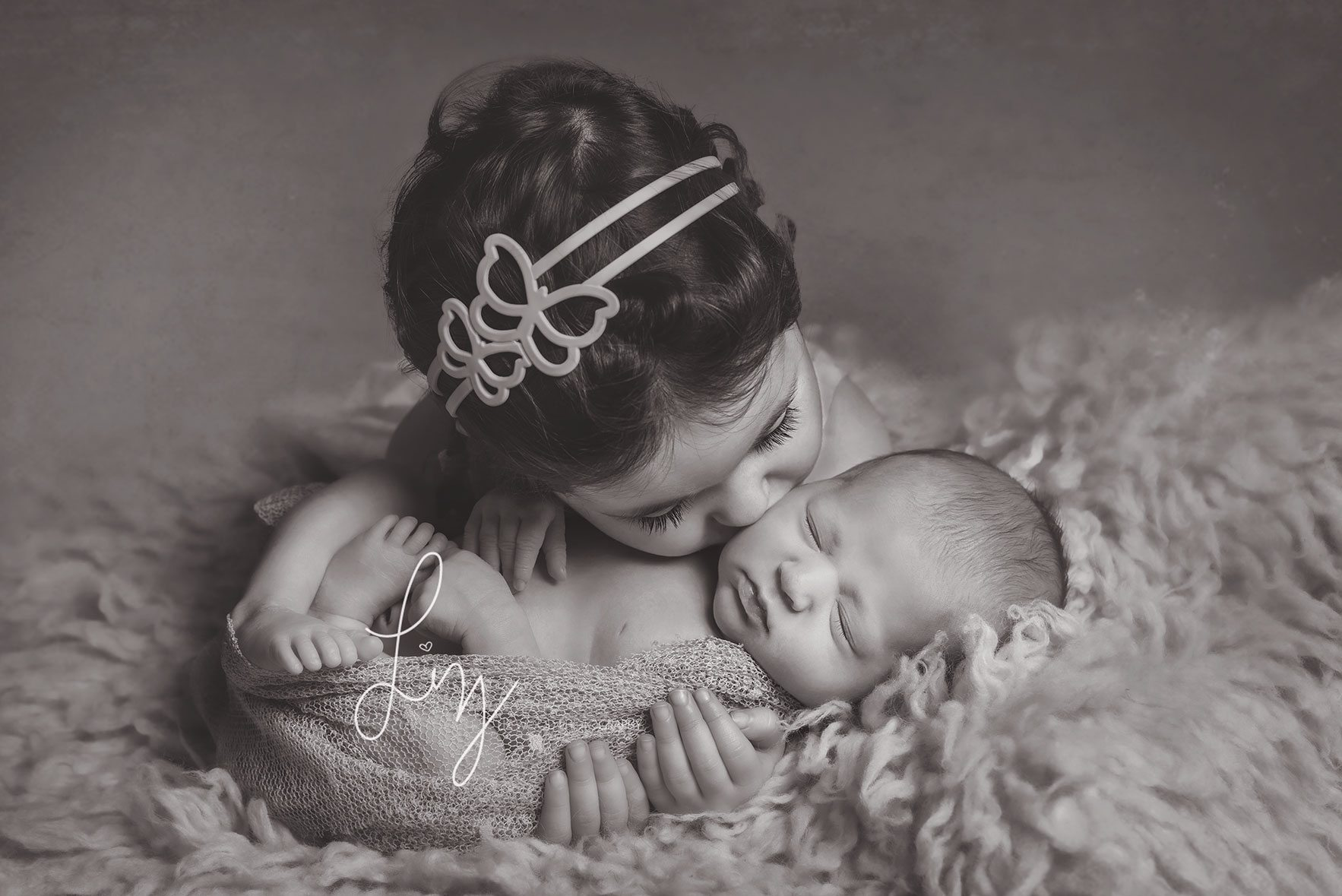 Sister cuddling her new baby sister on her newborn shoot - Essex newborn photographer