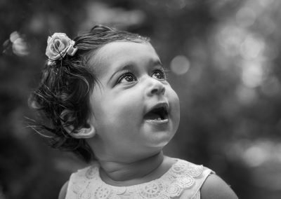 Black-and-white-photo-of-girl-in-park-looking-up-at-light