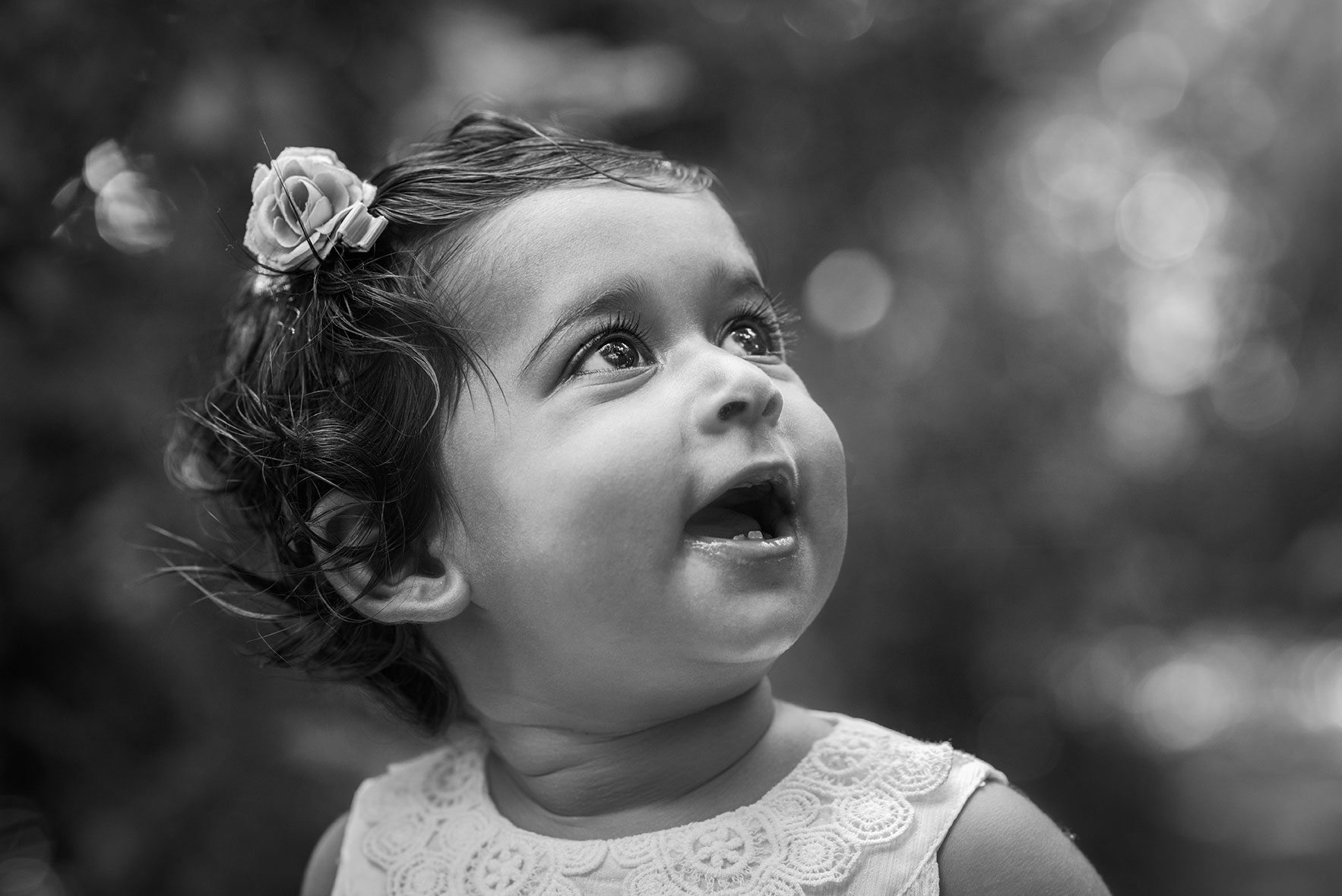 Outdoor photo of baby in black and white sitting side profile in Nowton Park, Bury St Edmunds