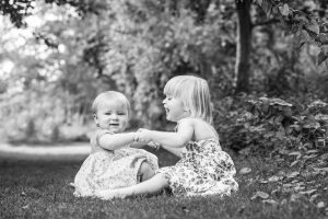 Black and white photo of two little girls playing row row your boat.