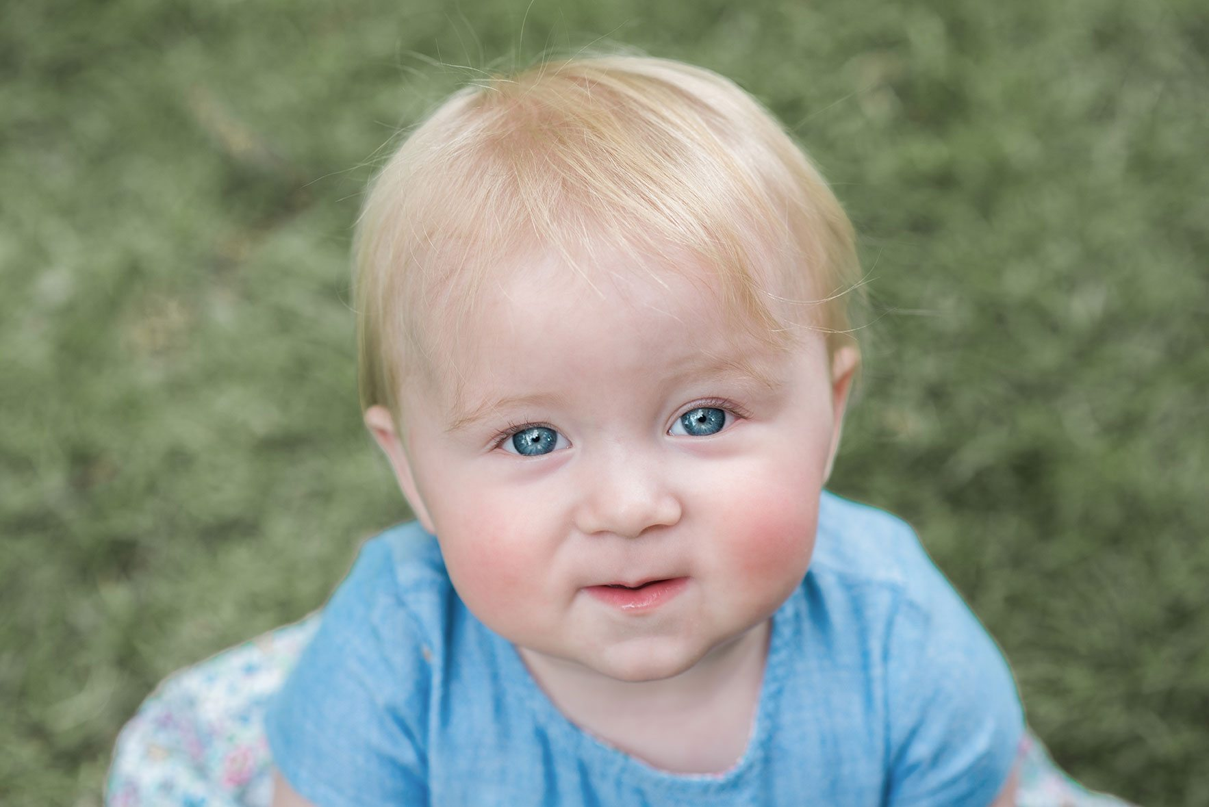Close up baby girl with blonde hair blue eyes outside looking up at camera in Halstead.