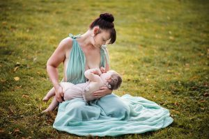 Breastfeeding Mum in a green gown, Bury St Edmunds breastfeeding outdoor photographer.