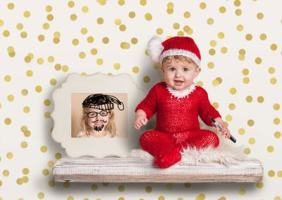 Elf-on-shelf-inspired-photoshoot---older-baby-in-knitted-Elf-outfit-drawing-on-his-sisters-photo-with-a-Sharpie-permanent-marker