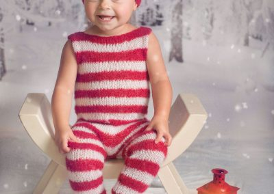 Elf-on-the-shelf-inspired-Christmas-shoot---girl-in-knitted-striped-Elf-suit-in-the-snow-with-a-lantern---Suffolk-child-photographer