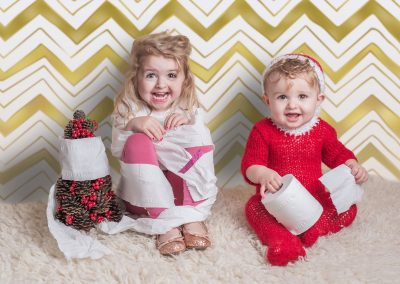 Elf-on-the-shelf-inspired-photo---little-Elf-wrapping-toilet-roll-round-his-sister---Bury-St-Edmunds-baby-and-child-photographer