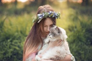 girl cuddling a ragdoll cat in meadows at sunset - Essex family photographer