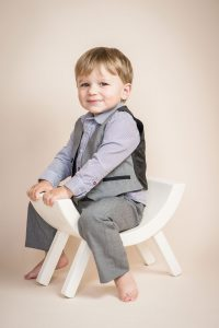 Boy sitting on curved stool in studio shoot cream background - Essex child & family photographer