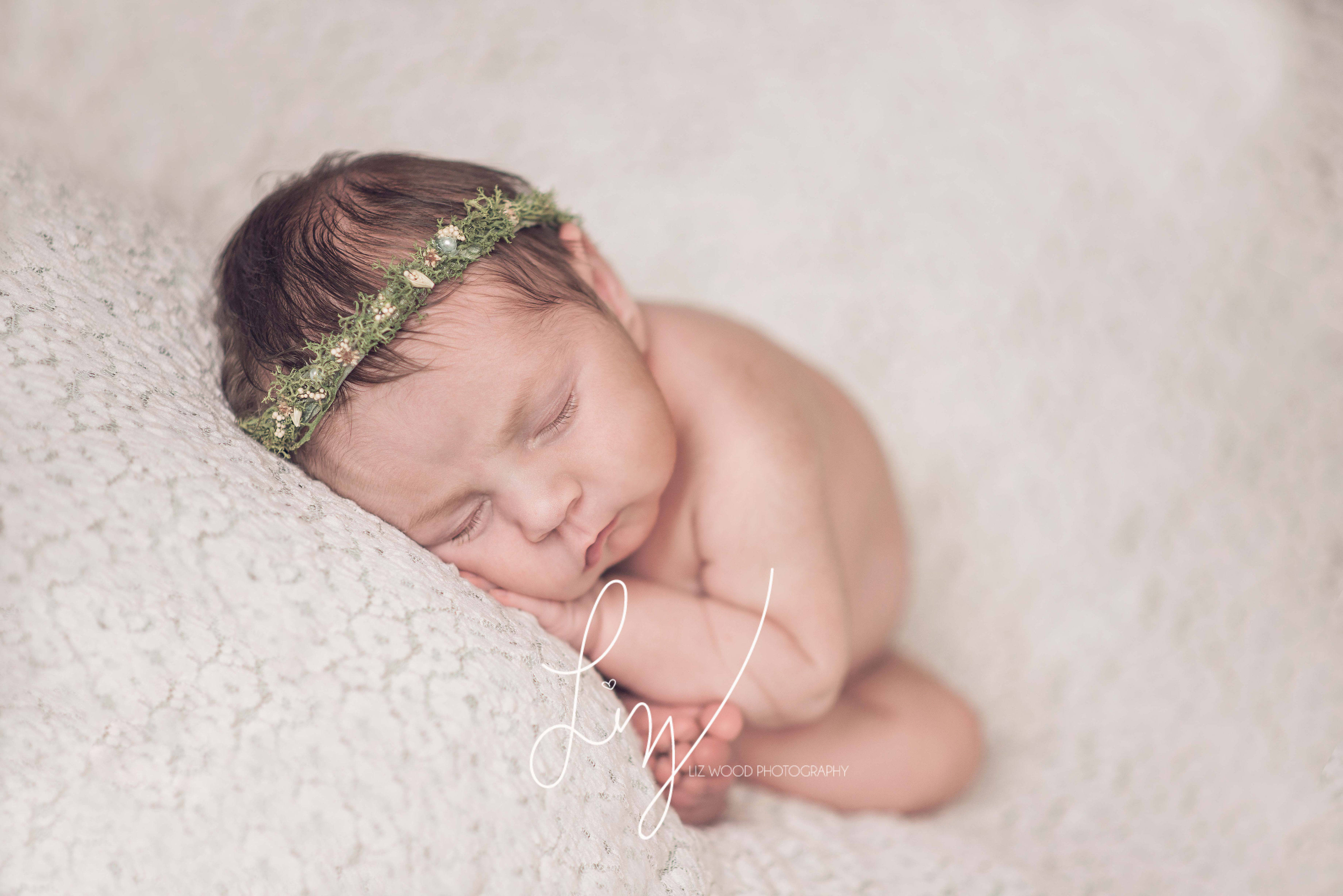 Baby girl laying on a cream lace backdrop - sweet simple newborn photographer in Essex and Suffolk
