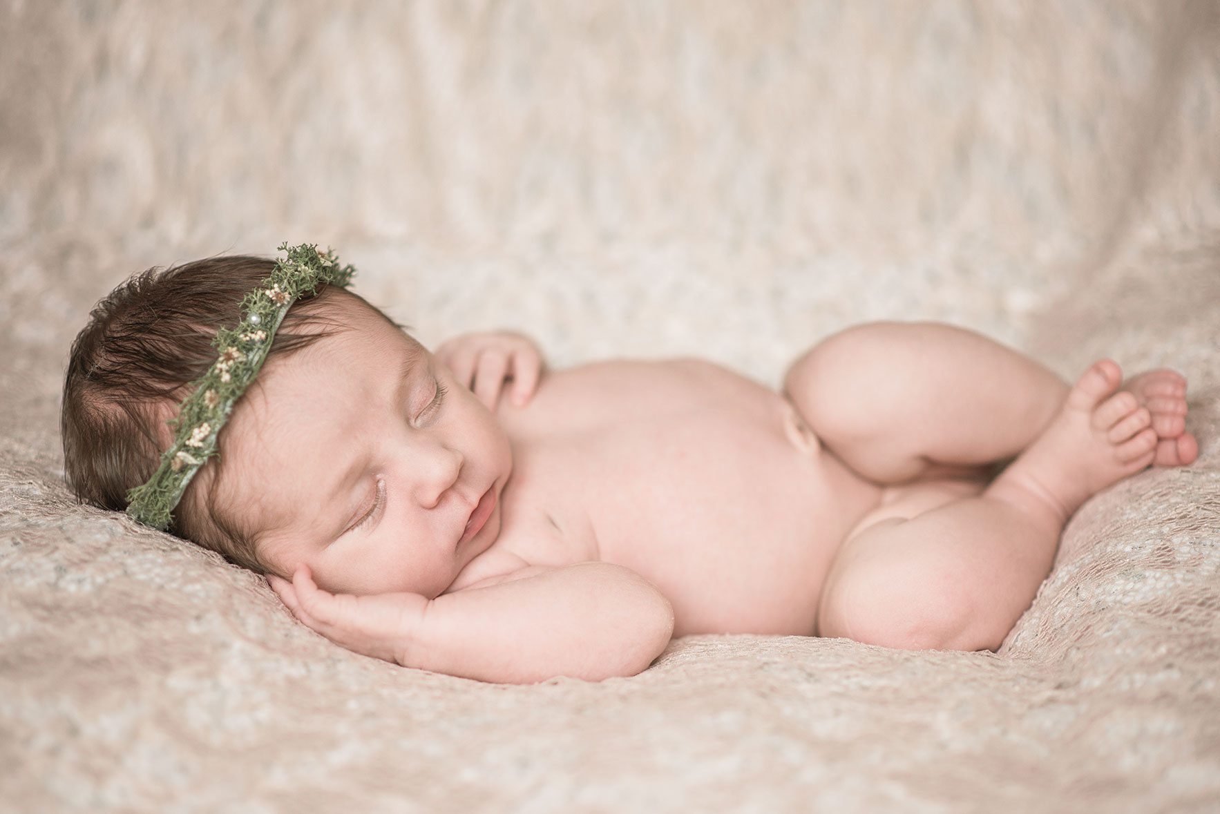 Baby girl laying on pink rug wearing a pretty headband - Essex baby photographer