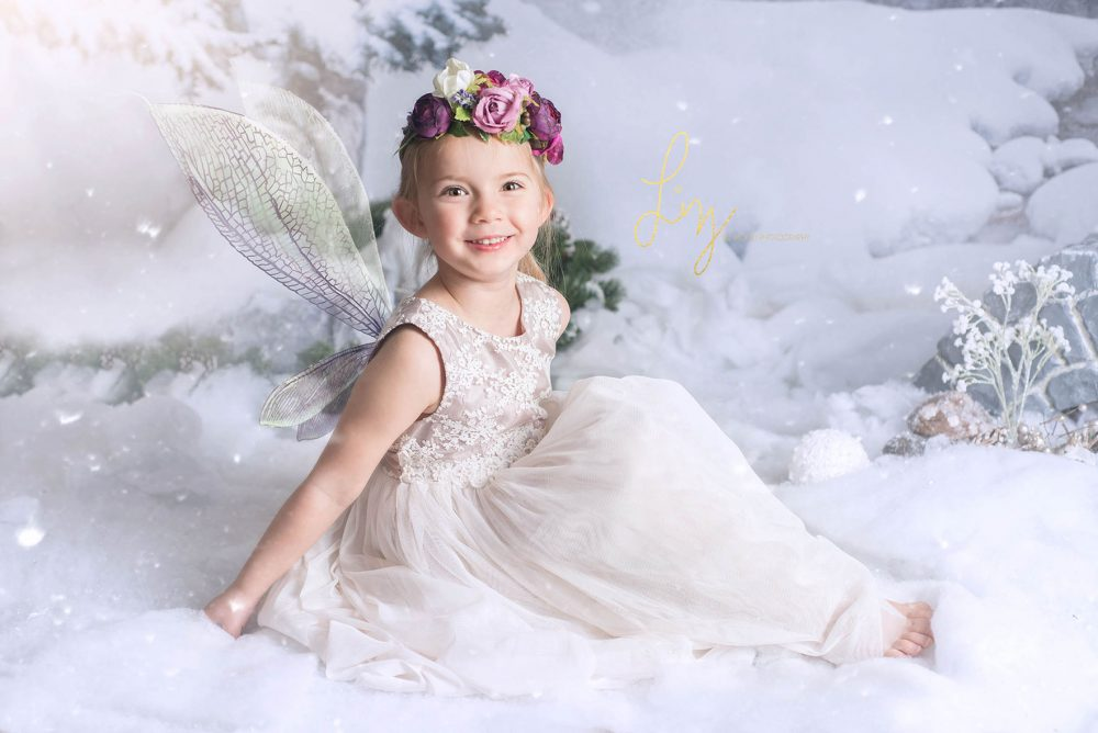 Girl sitting on snow scene with fairy wings - Essex fairy photographer.
