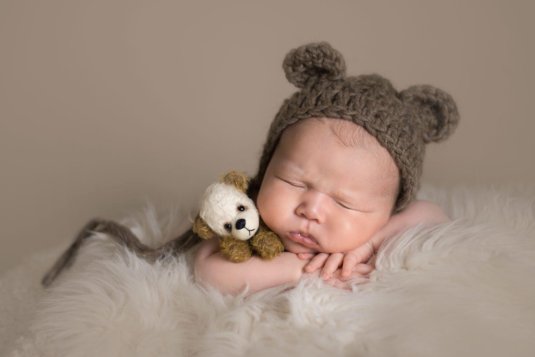 Essex newborn photographer - sweet baby boy cuddling a teddy bear.