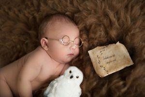Baby laying wearing tiny glasses - Harry Potter newborn photoshoot - Liz Wood creative baby photographer in Essex & Suffolk