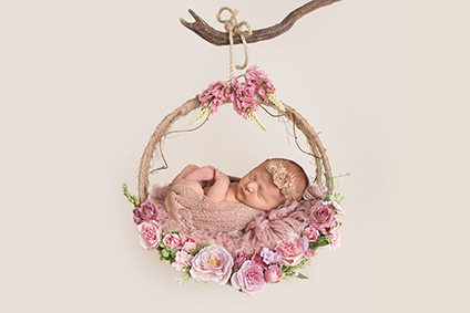 Suffolk baby photographer - newborn girl laying on flower hoop swing