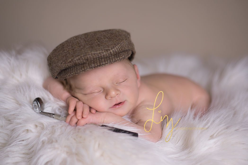 Suffolk baby laying with golf club tweed cap