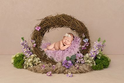 Baby laying in a wreath with lilac flowers - Essex baby photographer