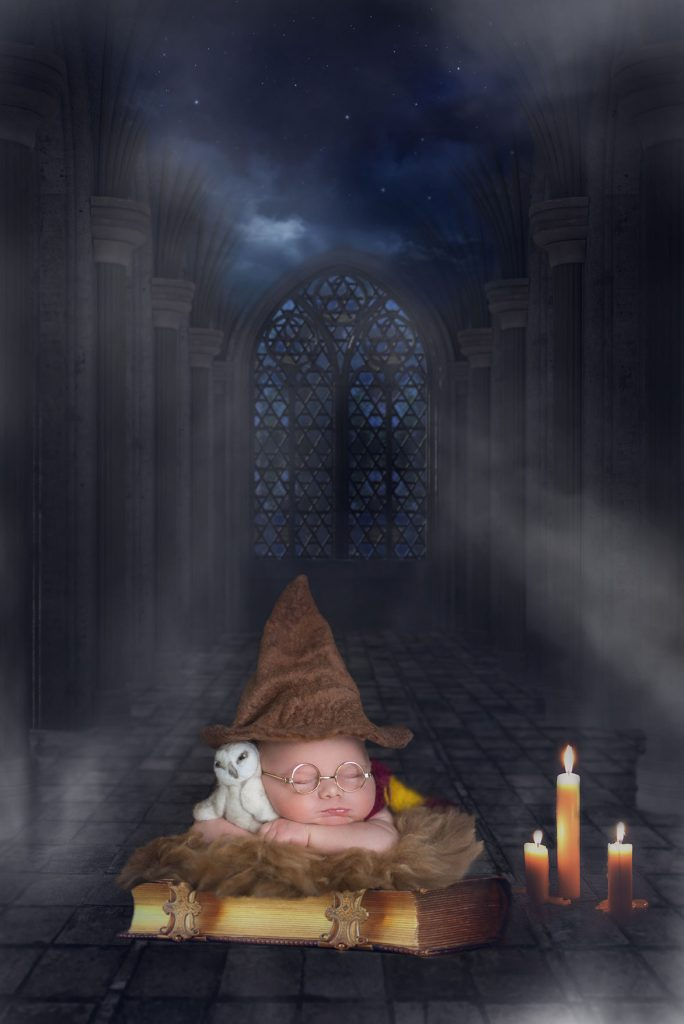 Baby laying wearing Sorting hat in the Enchanted dining room from Harry Potter