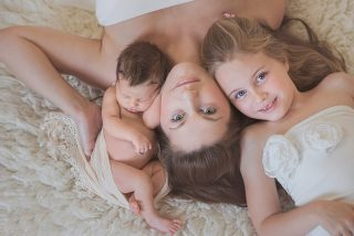 Baby photographer Essex - Family photo of Mum with older daughter and newborn baby laying looking up at camera.