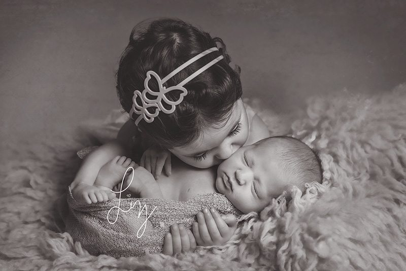 Sister kissing her newborn baby sister Essex Newborn Photographer