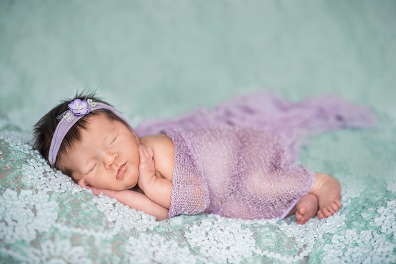 Chelmsford Essex Baby Photographer - baby laying on green backdrop newborn photo