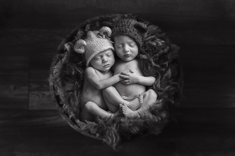 Twin boy and girl from Chelmsford on their newborn shoot holding hands in a wooden bowl. Essex baby photographer