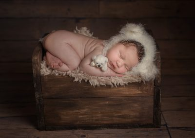 Essex baby photographer - baby dressed as bear on newborn bed