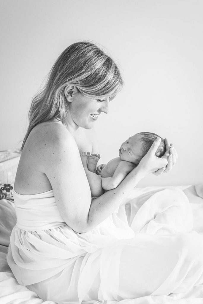 Mum sitting on bed holding new baby boy - Colchester baby photographer