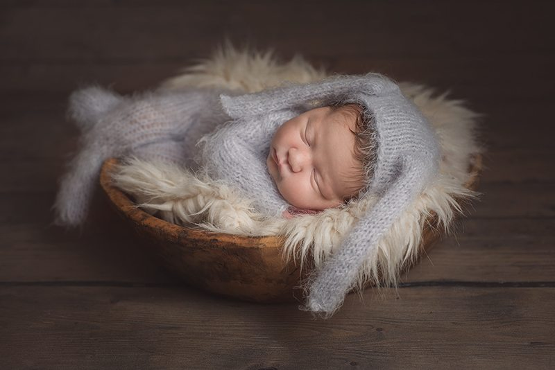 Beautiful little baby girl wearing a knitted rabbit outfit for her essex newborn shoot