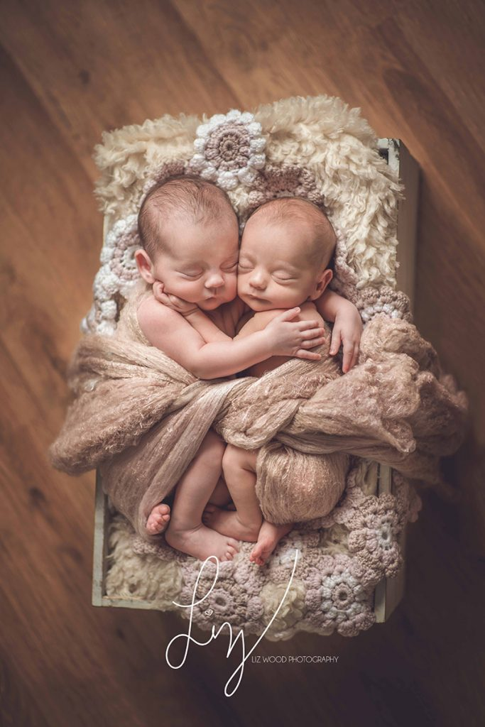 Essex Newborn Photographer twin girls cuddling in wooden crate