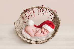 Beautiful baby boy in Santa hat - specialist Essex Newborn Photographer