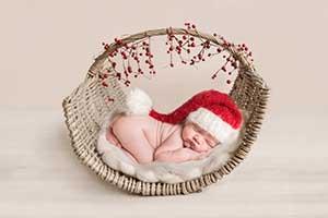Beautiful baby boy in Santa hat - specialist Essex Newborn Photographer