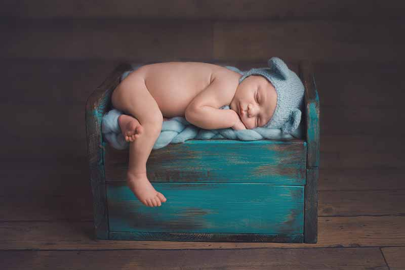 Essex newborn baby photos - baby sleeping on wooden bed
