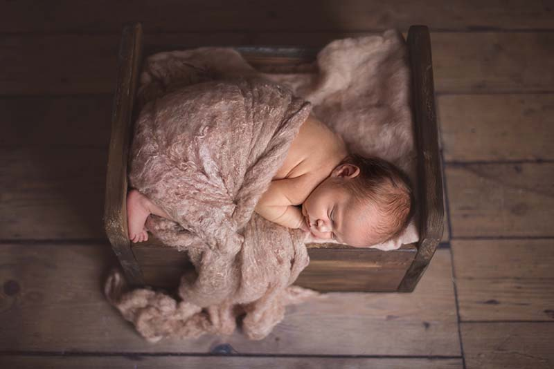 Little baby girl laying in crate - safe composite Sible Hedingham Essex Newborn Photography
