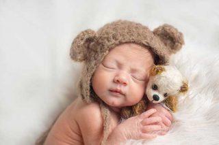 Really cute newborn girl in a bear hat cuddling a teddy - Essex newborn photographer